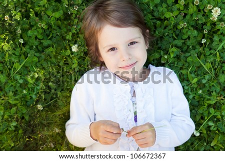 Little adorable girl lying on grass and smiling - stock photo