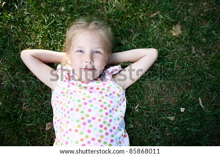 Little adorable girl  on the grass - stock photo