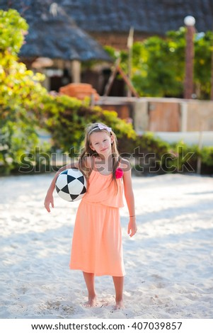 Little adorable girl playing voleyball on beach with ball - stock photo