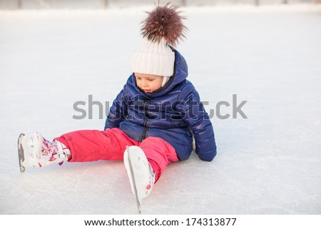 Little adorable girl sitting on ice with skates after the fall - stock photo