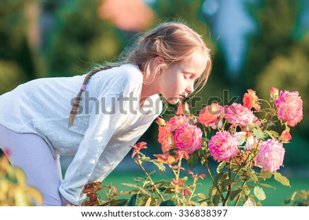 Little adorable girl smelling colorful flowers at summer day - stock photo