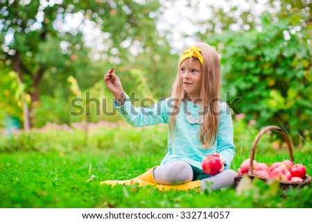 Little adorable girl with basket of red apples in sunny autumn day - stock photo