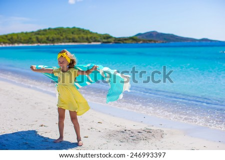 Little adorable girl with beach towel during tropical vacation - stock photo