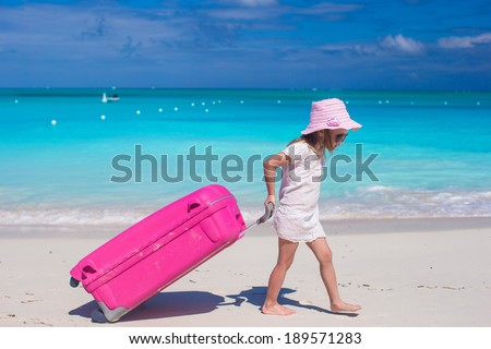 Little adorable girl with big colorful suitcase in hands walking on tropical beach - stock photo