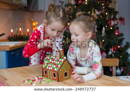 Little adorable girls decorating gingerbread house for Christmas - stock photo