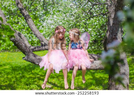 Little adorable girls sitting on blossoming tree in apple garden - stock photo