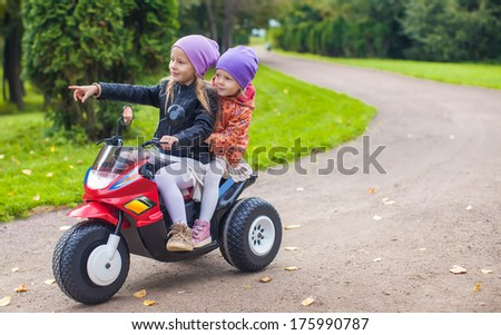 Little adorable sisters sitting on toy motorcycle in green park - stock photo