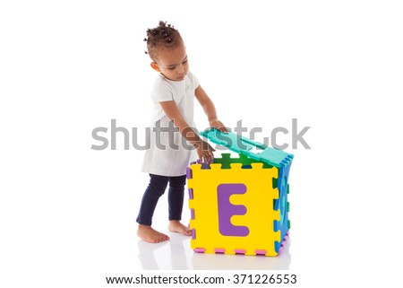 Little African American baby girl playing with construction games isolated on white background - stock photo