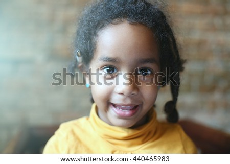 Little African girl is smiling and looking at camera.  - stock photo