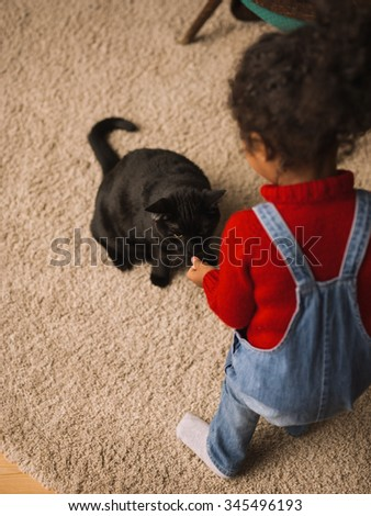 Little African Girl Playing with Cat at Home  - stock photo