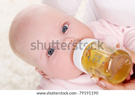 Little and cute baby, drinks from bottle with nipple - stock photo