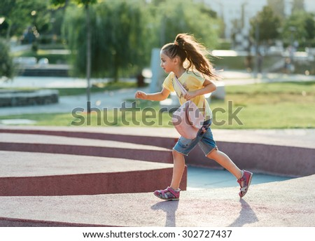 little and happy girl is running - stock photo