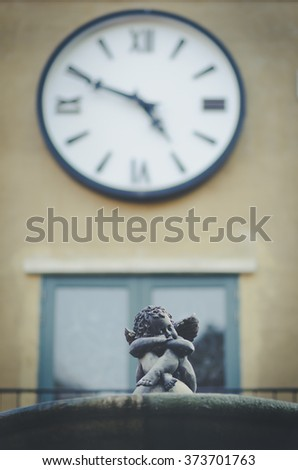 Little angel statue, blurry background, vintage tone. - stock photo