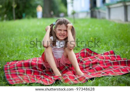 Little angry cute blond girl preschooler with ponytails sitting on the red plaid on green grass in summer - stock photo