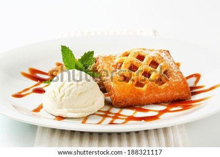 Little apricot pies with ice cream and drizzle sauce - stock photo