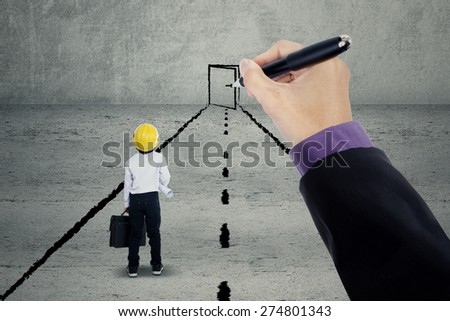 Little architect standing on a road while looking at a hand drawing a door - stock photo
