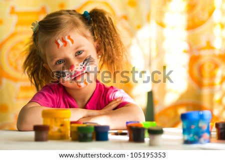 Little artist, drawing paint with paint of face. - stock photo