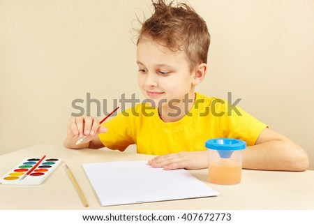 Little artist in a yellow shirt going to paint colors - stock photo