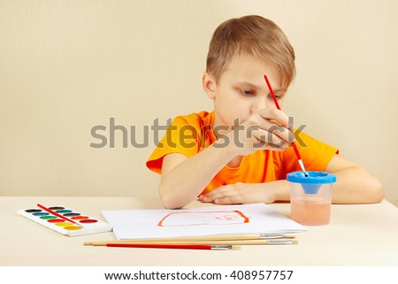 Little artist in an orange shirt painting colors - stock photo