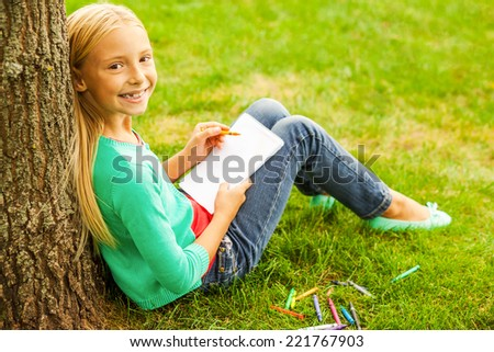 Little artist. Rear view of cute little blond hair girl drawing something at her note pad and looking over shoulder with smile while sitting on green grass and leaning at the tree  - stock photo
