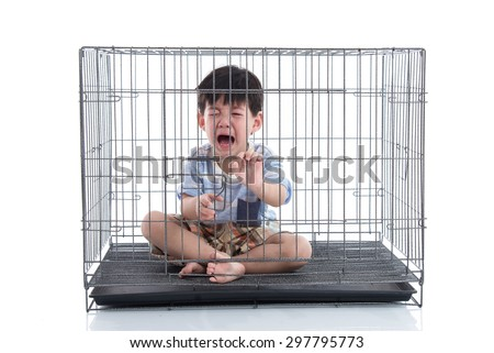 Little asian boy crying in a cage on white background isolated - stock photo