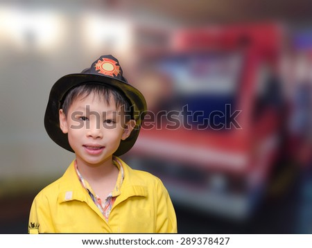 Little Asian boy in firefighter uniform in front of truck - stock photo