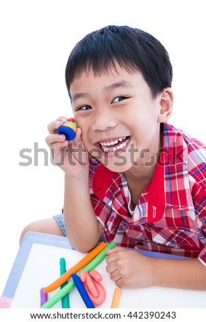 Little asian boy playing and creating toys from play dough. Child smiling and show his works from clay, on white background. Strengthen the imagination of child - stock photo