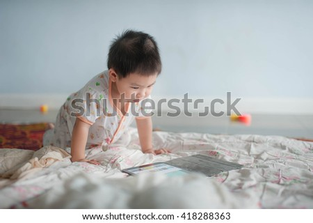 little asian boy playing digital tablet, early learning - stock photo