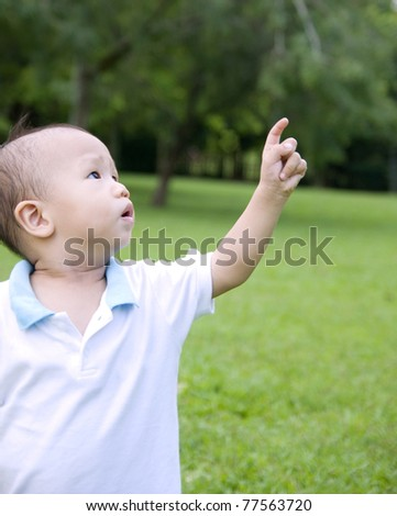 Little asian boy pointing to the sky - stock photo