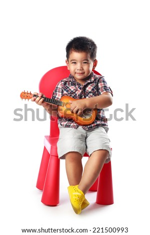 Little asian boy sits on a chair with a guitar, Isolated over white - stock photo