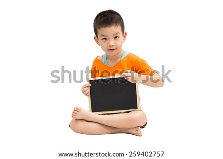 Little asian boy sitting and holding a blank blackboard isolated on white background - stock photo