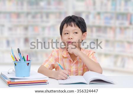 Little Asian boy thinking between doing homework  - stock photo