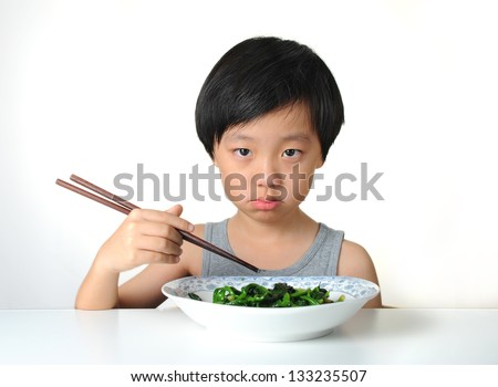 Little Asian boy unhappy to eat healthy food - stock photo