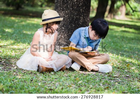 Little asian boy use pencil writing on notebook for writing book with smiling face in the park and younger sister looking to her brother - stock photo