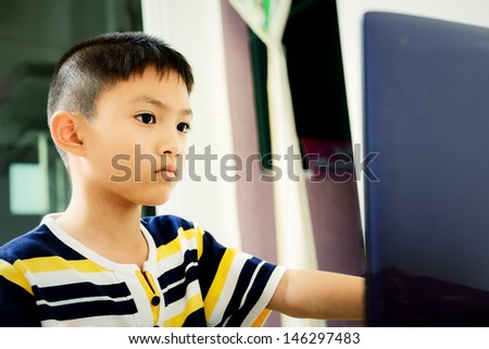 Little asian boy using laptop for knowledge - stock photo