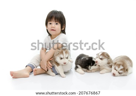 Little asian boy with puppies of siberian husky - stock photo