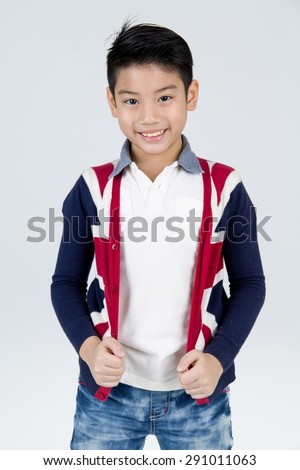 Little asian boy with smile face wearing winter clothes on gray background - stock photo