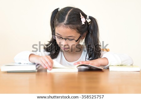 Little asian child girl wearing eyeglasses enjoy reading book w/ enjoyment (Selective focus): Lovely cute young female iq student kid studying w/ concentration in study room: Human rights to learn  - stock photo