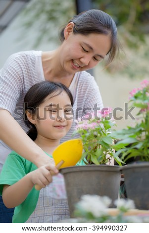 Little Asian child planting flower with her mother - stock photo