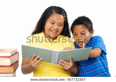 little asian couple kids doing homework  - stock photo