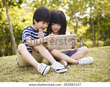 little asian girl and boy sitting on grass using digital tablet outdoors in a park. - stock photo
