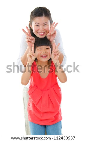Little Asian girl and mum gesture v hand sign, isolated on white background - stock photo