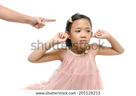 Little asian girl covering ears while mother scolding - stock photo