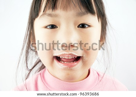 Little asian girl eating ice-cream/laughing - stock photo