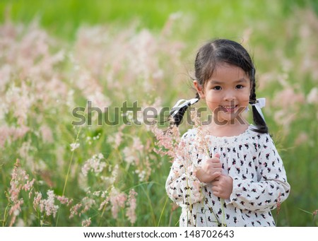 Little asian girl in a garden - stock photo