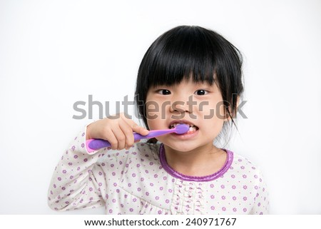 Little Asian girl in pyjamas brushing teeth - stock photo
