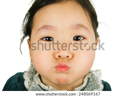 Little Asian girl inflates cheeks, isolated on white background. Close-up. - stock photo