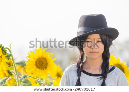 little Asian girl is looking the sunflower ,feel lonely and unhappy - stock photo