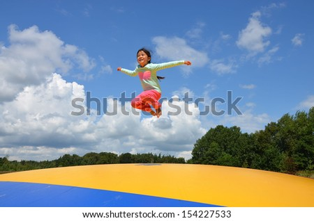 Little Asian girl jumping in the air - stock photo
