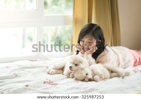 Little asian girl lying with two siberian husky puppies on bed - stock photo
